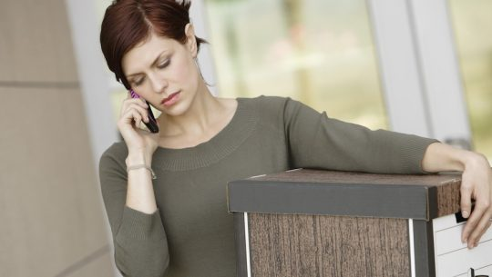 Career Transition Services | Woman on phone waling out with bankers box